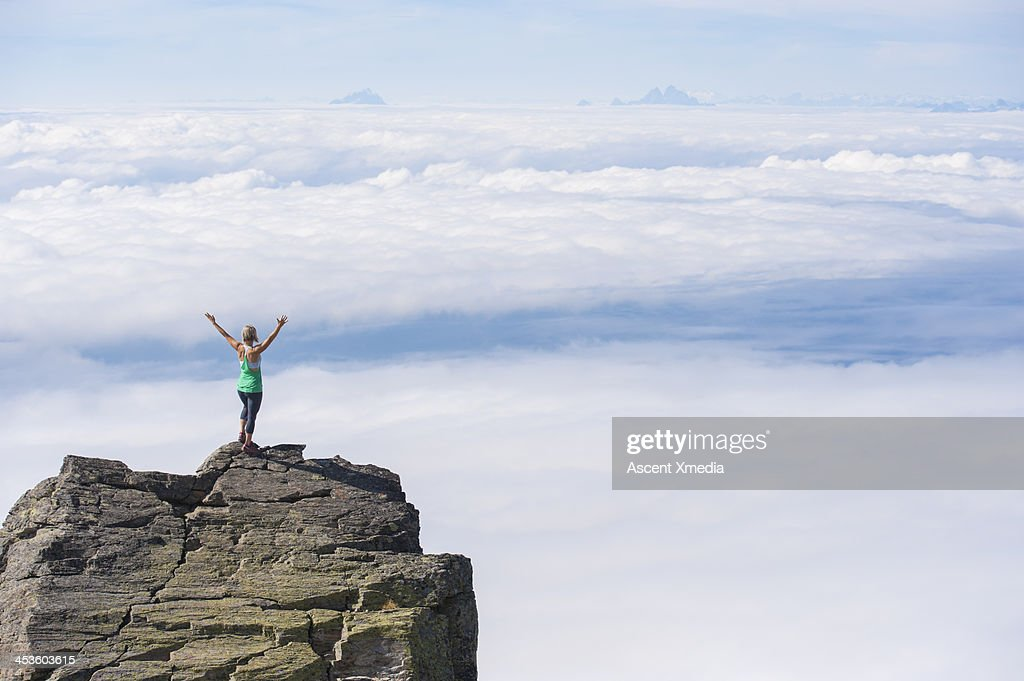 Woman stands on mt summit above clouds, arms out