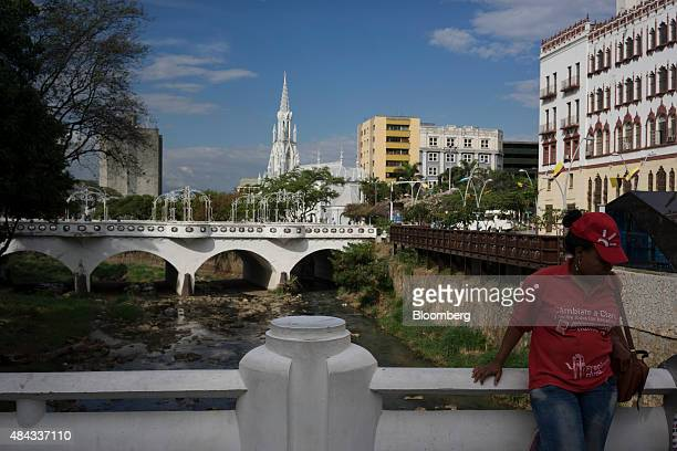 A woman stands on one of the bridges in downtown Cali Colombia on Wednesday Aug 12 2015 Colombia's central bank last month cut its forecast for 2015...