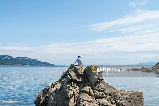 Woman stands on rock island, enjoying sea view