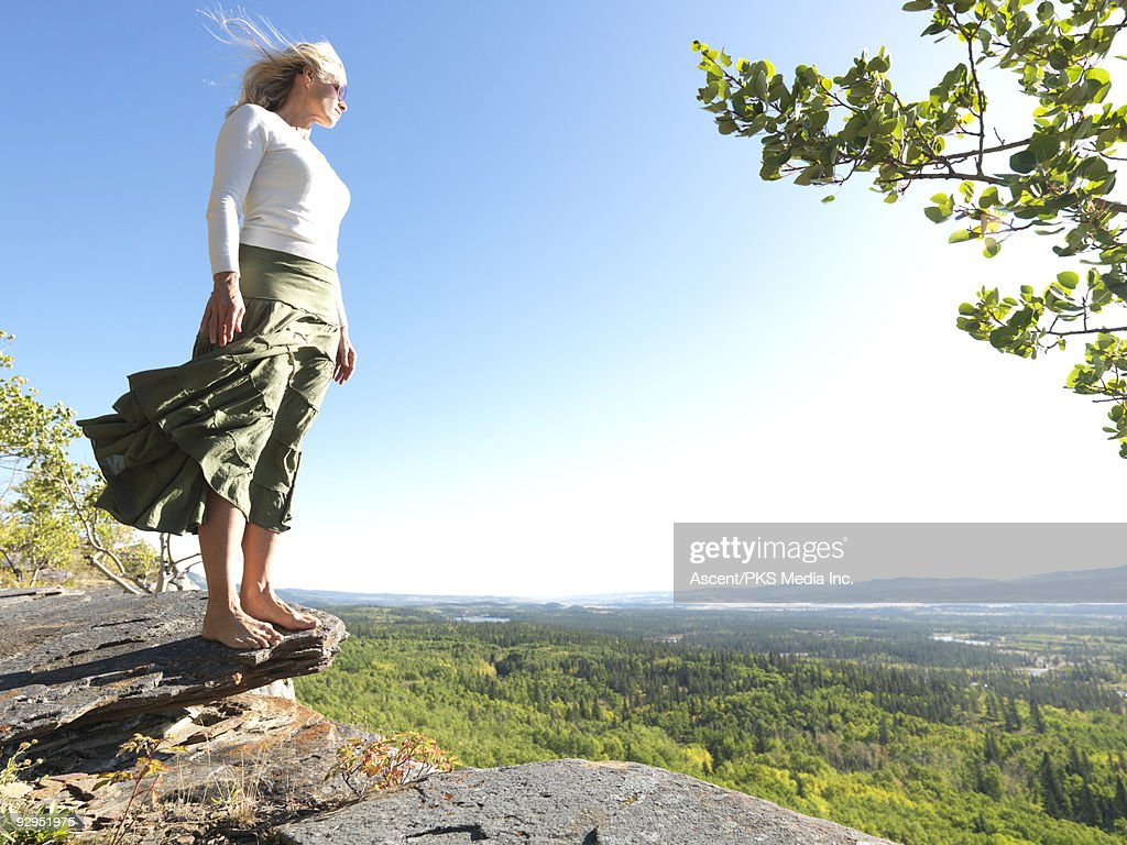 Woman stands on rock overlooking forest, windy day : Stock Photo