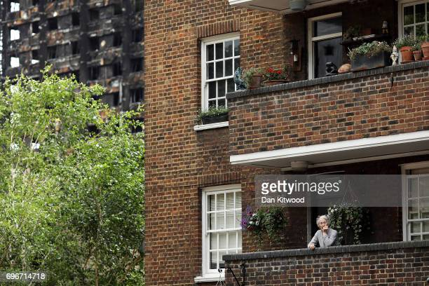 A woman stands on the balcony of her home close to Grenfell Tower on June 16 2017 in London England 30 people have been confirmed dead and dozens...