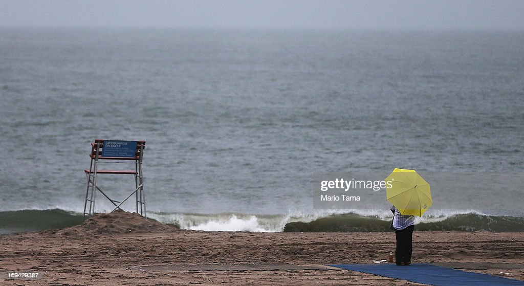 A woman stands on the beach at Coney Island, which was damaged by Hurricane Sandy, on May 24, 2013 in the Brooklyn borough of New York City. Coney Island and many other city beaches damaged by the storm will re-open to the public tomorrow.