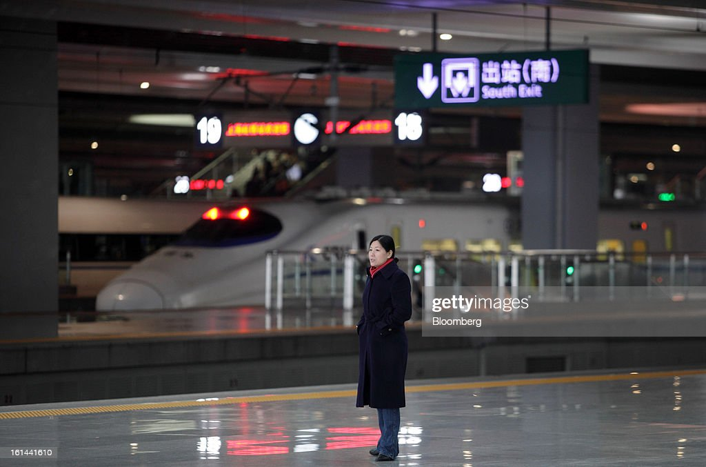 A woman stands on the platform in front of a China Railways high speed train parked at Hongqiao Railway Station in Shanghai, China, on Friday, Feb. 8, 2013. A record 3.41 billion passenger trips may be made this year during the Lunar New Year period, according to the National Development and Reform Commission. Photographer: Tomohiro Ohsumi/Bloomberg via Getty Images