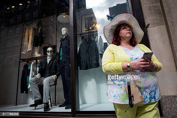A woman stands on the sidewalk during the Easter Parade and Bonnet Festival along 5th Avenue March 27 2016 in New York City The parade is a New York...