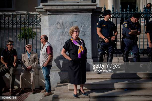 TOPSHOT A woman stands on the stairs outside the Administrative Court in Athens as she takes part in a protest against planned pension cuts on...