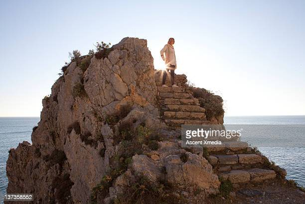 Woman stands on top of stone staircase, sea behind