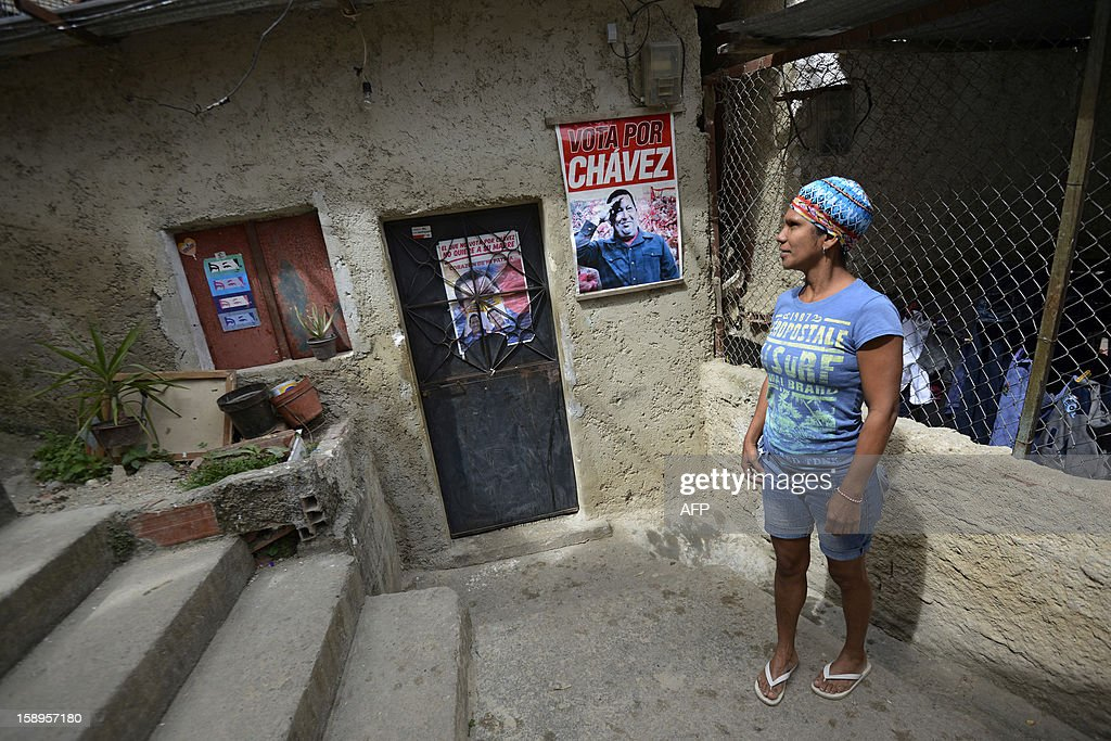 A woman stands outside her home next to posters of Venezuelan President Hugo Chavez in the popular sector of San Agustin, in Caracas on January 4, 2013. Hugo Chavez's top aides have gone on the offensive, accusing the opposition and media of waging a 'psychological war,' as Venezuela's cancer-stricken president battles a serious lung infection. The closing of ranks followed a high-level gathering of top Venezuelan officials in Havana with Chavez, amid growing demands to know whether he will be fit on January 10 to take the oath of office for another six-year-term. AFP PHOTO/Leo Ramirez
