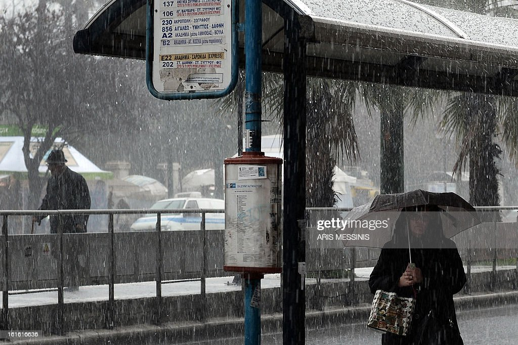 A woman stands under a bus station during a heavy rainfall in central Athens on February 13, 2013.
