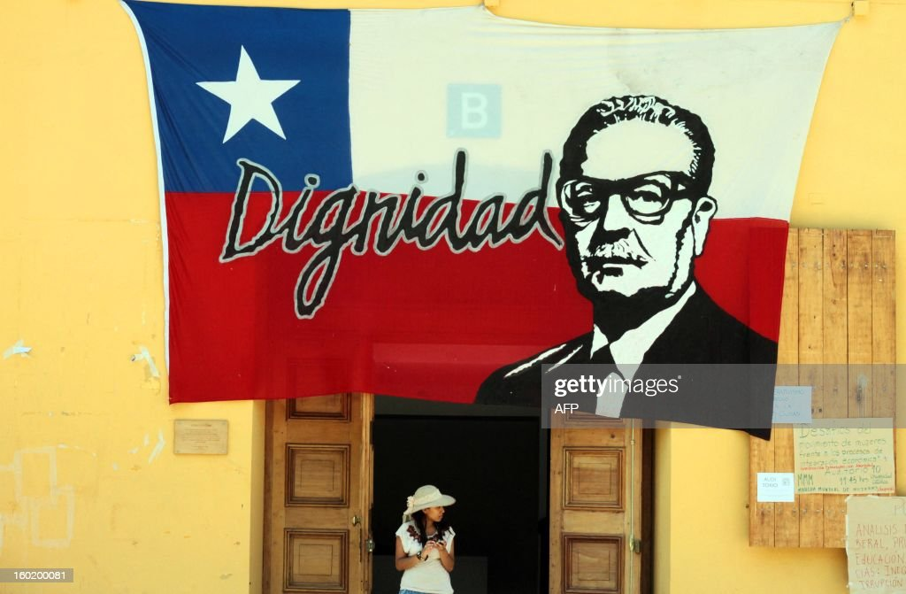A woman stands under a Chilean flag with an image of late president Salvador Allende during the People's Summit being held in Santiago the sidelines of the Latin American and Caribbean States (CELAC)-European Union (EU) Summit, on January 27, 2013. European and Latin American leaders have pledged to shun protectionism and boost their strategic partnership to foster free trade and sustainable development based on close international cooperation. Some 60 countries are represented at the summit between the 27-member European Union and the Community of Latin American and Caribbean States, or CELAC. AFP PHOTO / RODRIGO SAENZ