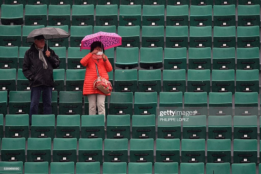 A woman stands under an umbrella in the stands as rains falls over the Roland Garros stadium during the Roland Garros 2016 French Tennis Open in Paris on May 31, 2016. / AFP / PHILIPPE