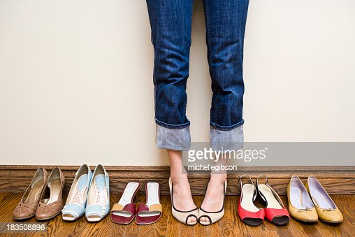 Woman stands wearing heels with her collection of Shoes