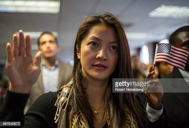 A woman stands while taking the oath to become a US citizen at the New York District office of the US Citizenship and Immigration Services November...