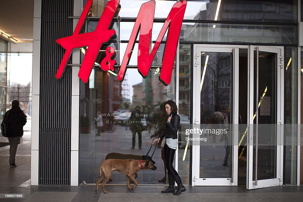 A woman stands with a dog on a lead outside the entrance to a Hennes & Mauritz AB (H&M) store in Warsaw, Poland, on Thursday, April 11, 2013. Poland's central bank kept interest rates unchanged at a record-low 3.25 percent yesterday. Photographer: Bartek Sadowski/Bloomerg