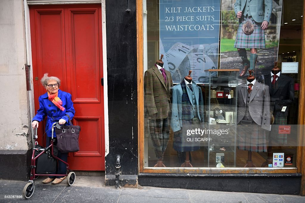 A woman stands with a walking aid as she waits near a shop selling formal menswear, including tartan kilts, in Edinburgh, Scotland on June 27, 2016. British leaders battled to calm markets and the country Monday after its shock vote to leave the EU, while insisting London would be not rushed into a quick divorce. Britain's historic decision to be the first country to leave the 28-nation bloc has fuelled fears of a break-up of the United Kingdom with Scotland eyeing a new independence poll, and created turmoil in the opposition Labour party where leader Jeremy Corbyn is battling an all-out revolt. / AFP / OLI