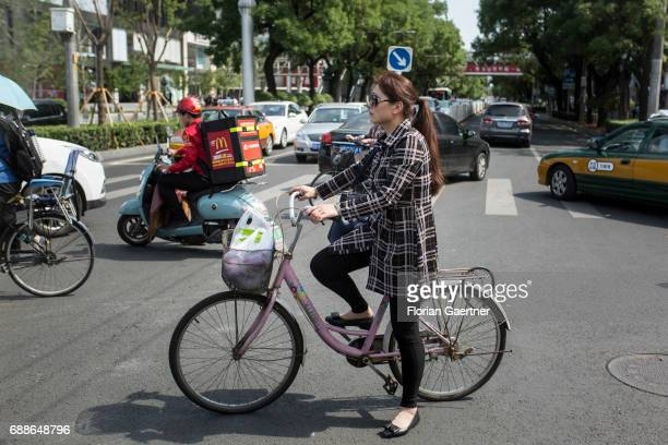 A woman stands with her bicycle in the middle of a street crossing during a traffic jam on May 24 2017 in Beijing China