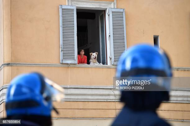 A woman stands with her dog at the window of a building overlooking a demonstration against the European Union on March 25 2017 in Rome Italian...