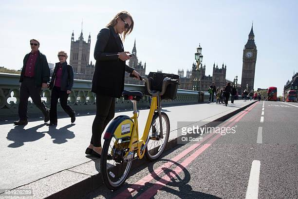 A woman stands with her specially painted yellow London Cycle Hire scheme bike on Westminster Bridge on April 15 2014 in London England 101 of the...