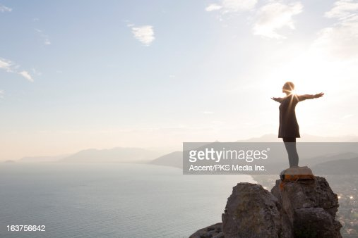 Woman stands with outstretched arms, sea below
