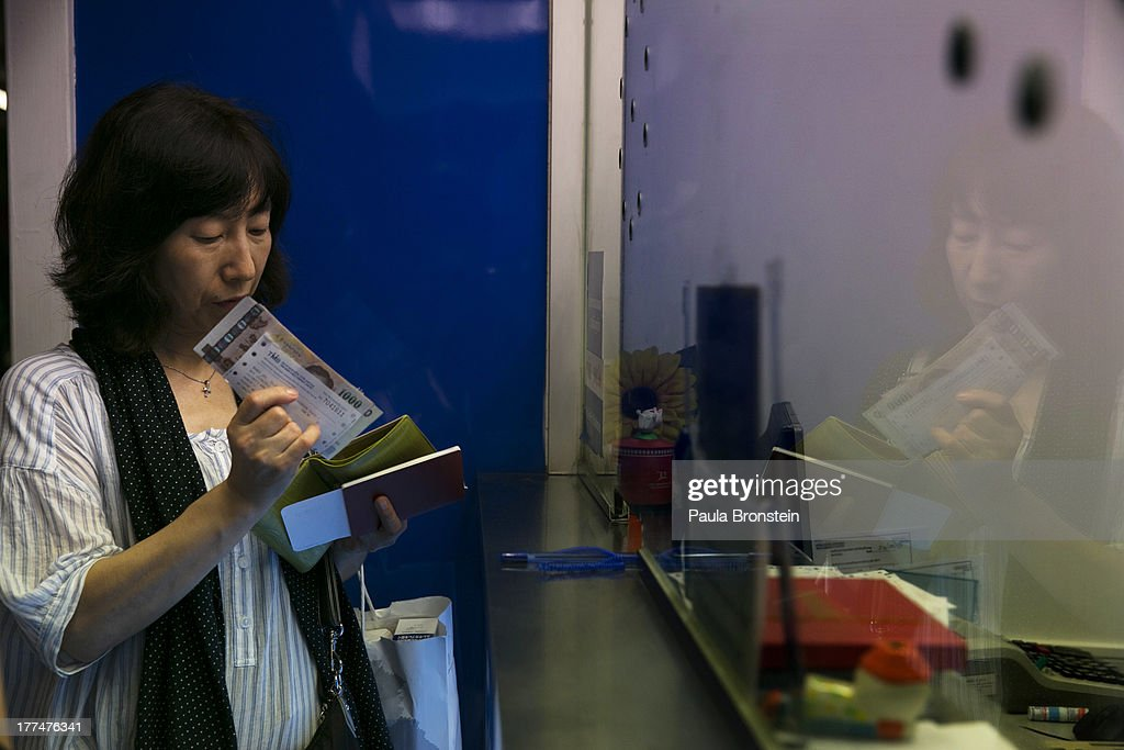 A woman staqnds near a money exchange bank kiosk on August 23, 2013 in downtown Bangkok, Thailand. The local currency dropped to its lowest level since August 2010. Against the US dollar the Thai baht fell to 32.09/32.13 dropping about 5% this year.