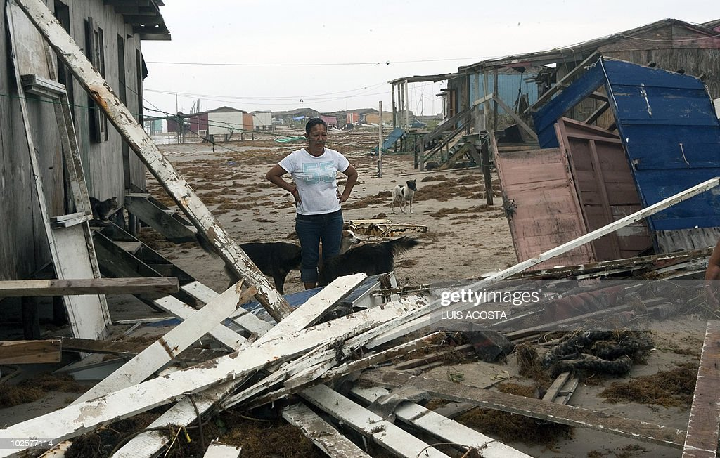 A woman stares at her damaged house after the passage of Hurricane Alex in Bagdad Beach, in Matamoros, Tamaulipas State, on July 1, 2010. Alex, the first hurricane of the Atlantic season, weakened across northeast Mexico as it neared high mountains on Thursday, after disrupting oil clean-up operations in the Gulf of Mexico. Alex was downgraded to a tropical storm after roaring ashore late Wednesday as a Category Two hurricane slightly south of the eastern US-Mexico border. AFP PHOTO/Luis Acosta