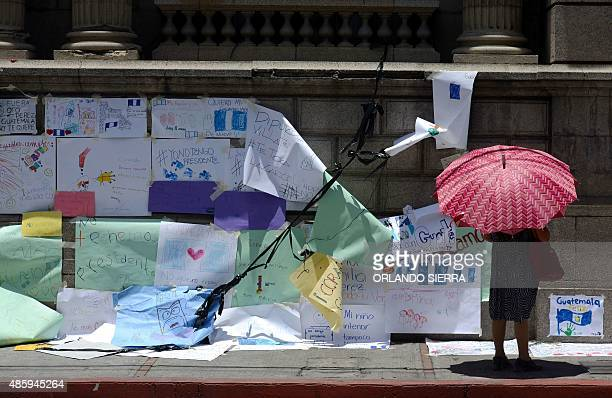A woman stares at signs against President Otto Perez Molina stuck on the eve by demonstrators at the Congress building in Guatemala City on August 30...