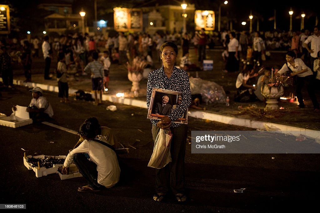 A woman stares at the portrait of former King Norodom Sihanouk posted on the outside of the Royal Palace after the cremation ceremony for former King Norodom Sihanouk on February 4, 2013 in Phnom Penh, Cambodia. The former King's cremation ceremony comes on the fourth day of a seven day royal funeral ceremony and nearly four months since his death in Beijing last October. Foreign leaders from 16 countries attended the cremation ceremony.