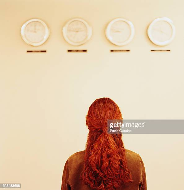 Woman Staring at Clocks Set to Different Time Zones