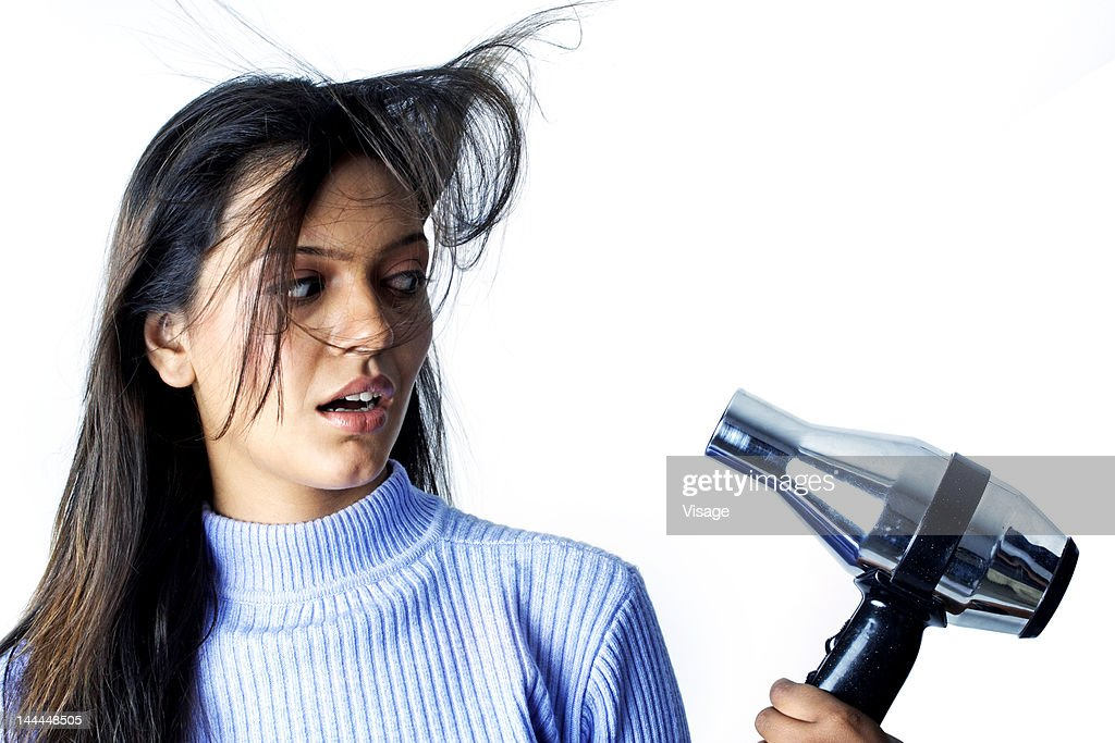 Woman startled at the sight of a blow dryer : Stock Photo