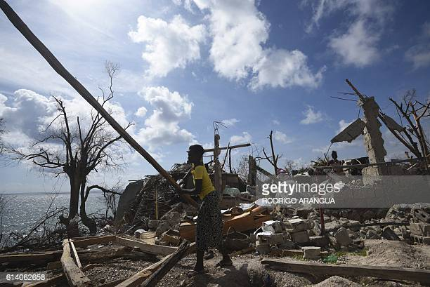 A woman starts to repair her home destroyed by Hurricane Matthew in Port Salut southwest of PortauPrince on October 11 2016 Haiti faces a...