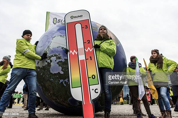 A woman stays in front of a model of the earth holding a thermometer as activists participate in the Global Climate March on November 29 2015 in...