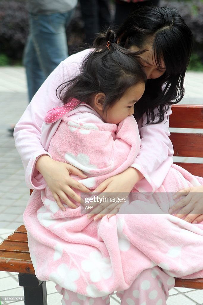 A woman stays outside to take shelter with a girl in her arms in Chongqing, southwest China's Sihchuan province, as a shallow earthquake struck close to the city of Ya'an on the edge of the Tibetan Plateau just after 8:00 am (0000 GMT), setting off landslides, destroying buildings and triggering a major rescue operation on April 20, 2013. 72 people were killed when the earthquake struck China's southwestern Sichuan province on April 20, local officials said, five years after a massive quake devastated the region. CHINA