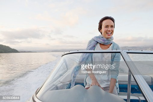 Woman steering motorboat : Stockfoto