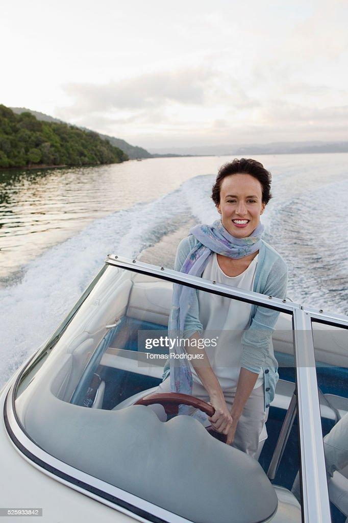 Woman steering motorboat : Stock Photo