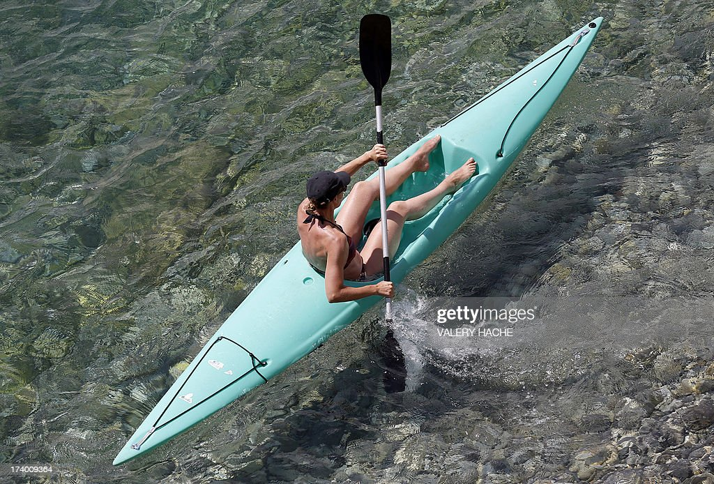 A woman steers her kayak on shore of the French southeastern city of Nice on July 19, 2013.