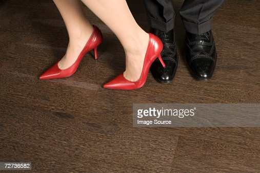 Woman stepping on a mans foot : Stock Photo