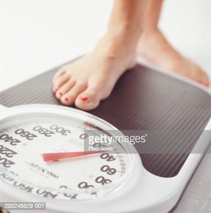 Woman stepping on bathroom scale, low section, Close-up of foot : Stock Photo
