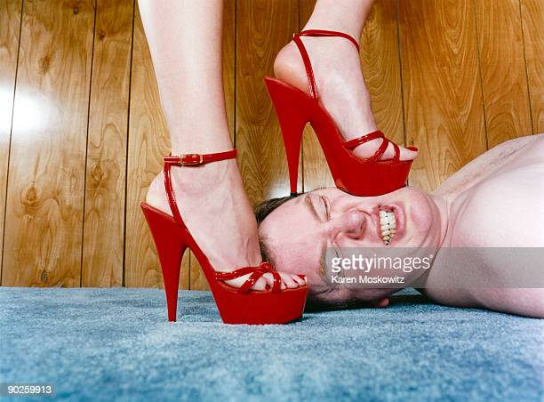 Woman stepping on man