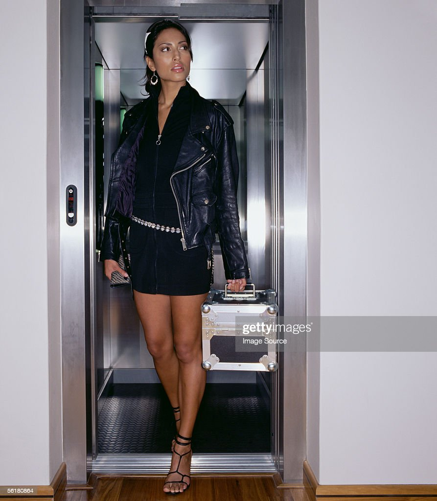 Woman stepping out of an elevator : Stock Photo