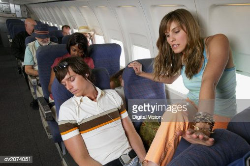 Woman Stepping Over a Man Sleeping in His Seat on a Commercial Aeroplane : Stock-Foto