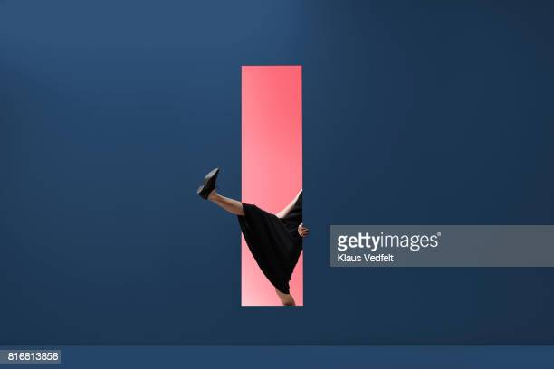 Woman stepping threw rectangular opening of coloured wall
