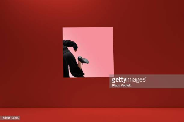 Woman stepping threw square opening in coloured wall