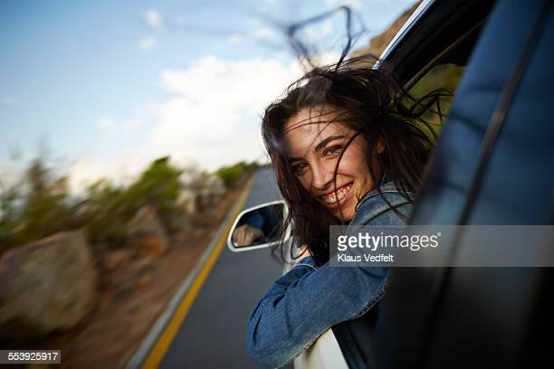 Woman sticking head out of car in motion
