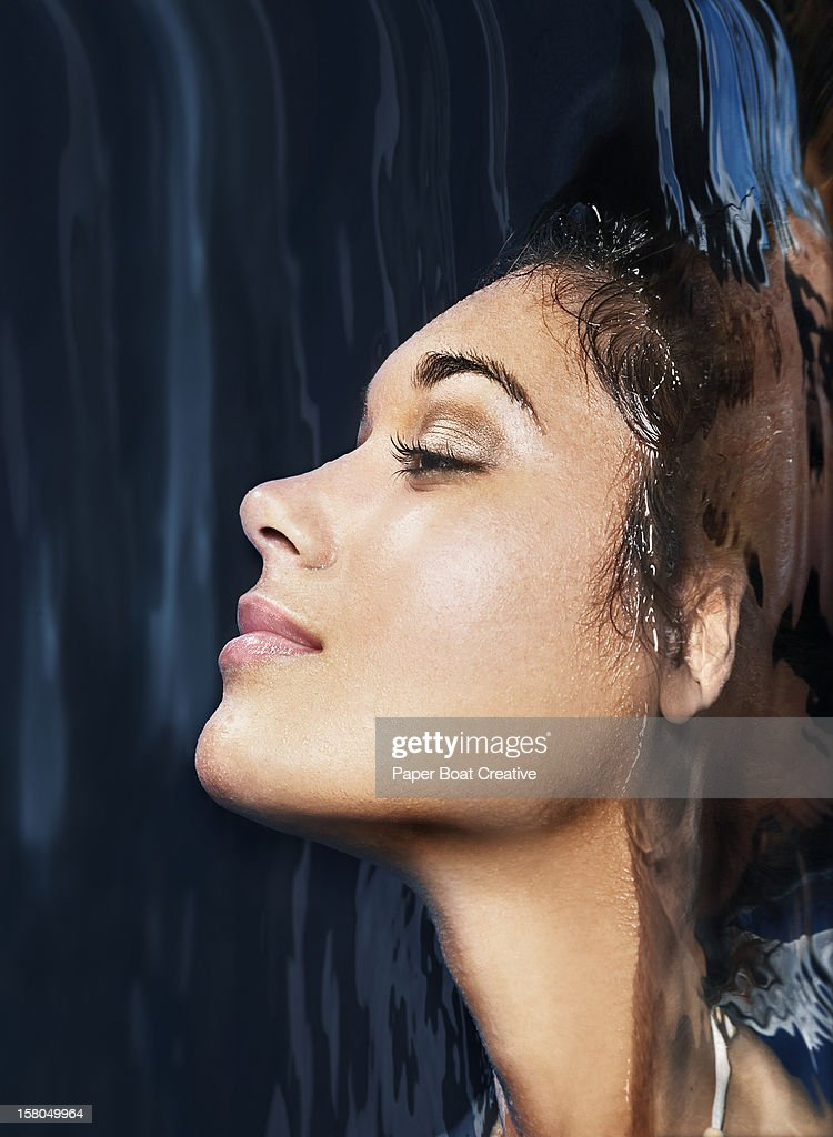 woman sticking her head out of a pool of water : Stock Photo