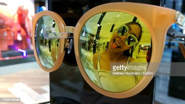 Woman Sticking Out Tongue Reflecting On Sunglasses At Shopping Mall
