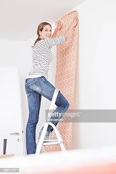 Woman sticking wallpaper on wall