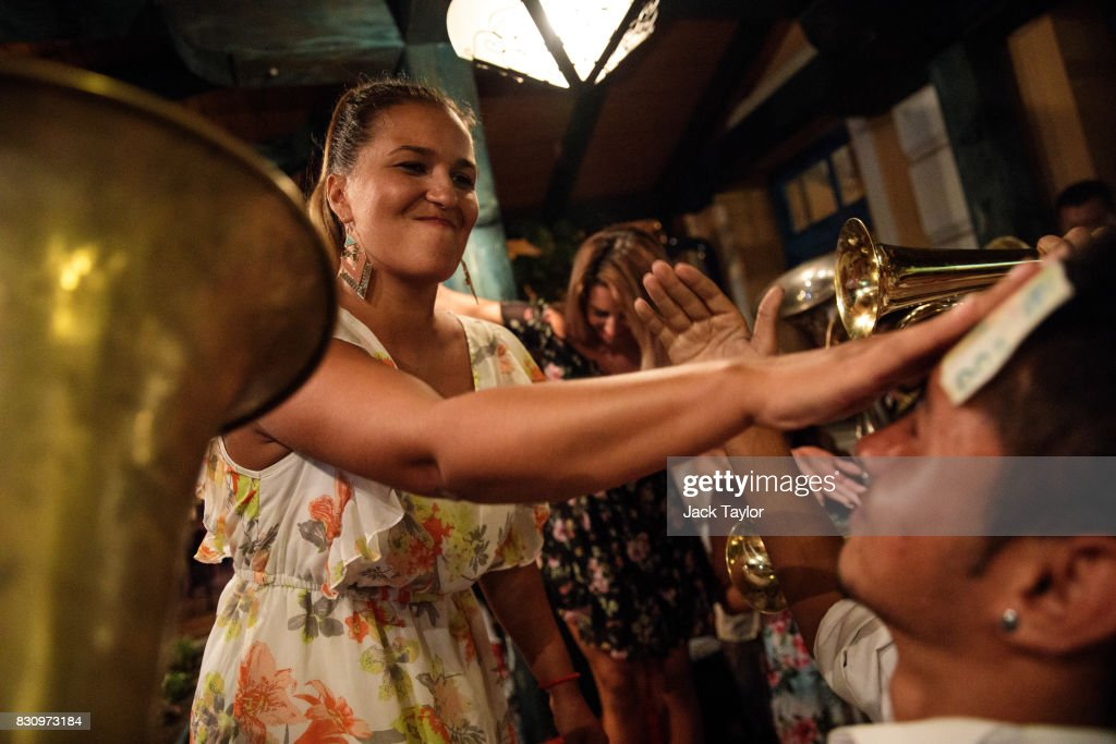 A woman sticks a 500 Serbian Dinar note onto the forehead of a musician after playing in a restaurant during the Guca Trumpet Festival on August 11, 2017 in Guca, Serbia. Thousands of revellers attend the trumpet festival, held annually since 1961 in the small, central Serbian town of Guca. The free event is a celebration of Balkan music with dozens of orchestras and solo trumpeters taking part in the festival's main competition. During the festival wild street parties take place throughout the night as brass bands parade and play for tips to the thousands of visitors in the town's restaurants, bars and pop-up tents.