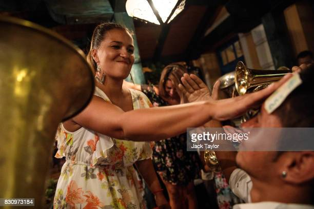 A woman sticks a 500 Serbian Dinar note onto the forehead of a musician after playing in a restaurant during the Guca Trumpet Festival on August 11...