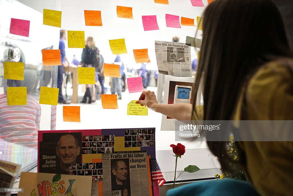 A woman sticks a Post-it note on a window at a memorial for Steve Jobs, co-founder and former chief executive officer of Apple Inc., outside an Apple store in New York, U.S., on Thursday, Oct. 6, 2011. Jobs, who built the world's most valuable technology company by creating devices that changed how people use electronics and revolutionized the computer, music and mobile-phone industries, died on Oct. 5. He was 56. Photographer: Stephen Yang/Bloomberg via Getty Images