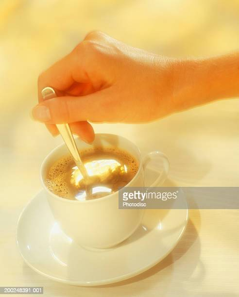 Woman stirring coffee, Close-up of hand