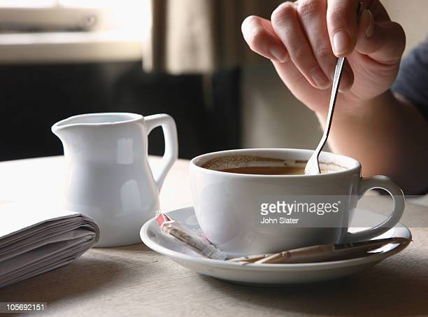 woman stirring her coffee at table